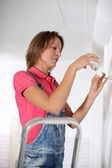 Donna in piedi sulla scala di difficoltà lampadina — Foto Stock