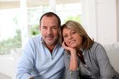 Portrait of happy senior couple sitting in sofa — Stock Photo