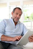 Senior man at home using electronic tablet — Stock Photo