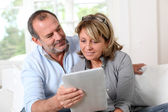 Senior couple looking at web pages on electronic tablet — Stock Photo