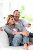 Starší pár, sledování televize doma — Stock fotografie