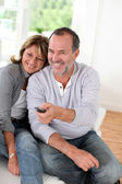 Senior couple watching televion at home — Stockfoto