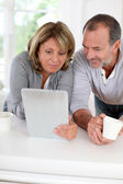 Senior couple drinking coffee in front of tablet — Stock Photo