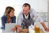 Senior couple having fun in home kitchen — Stock Photo