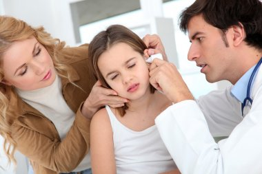 Doctor looking at little girl ear infection
