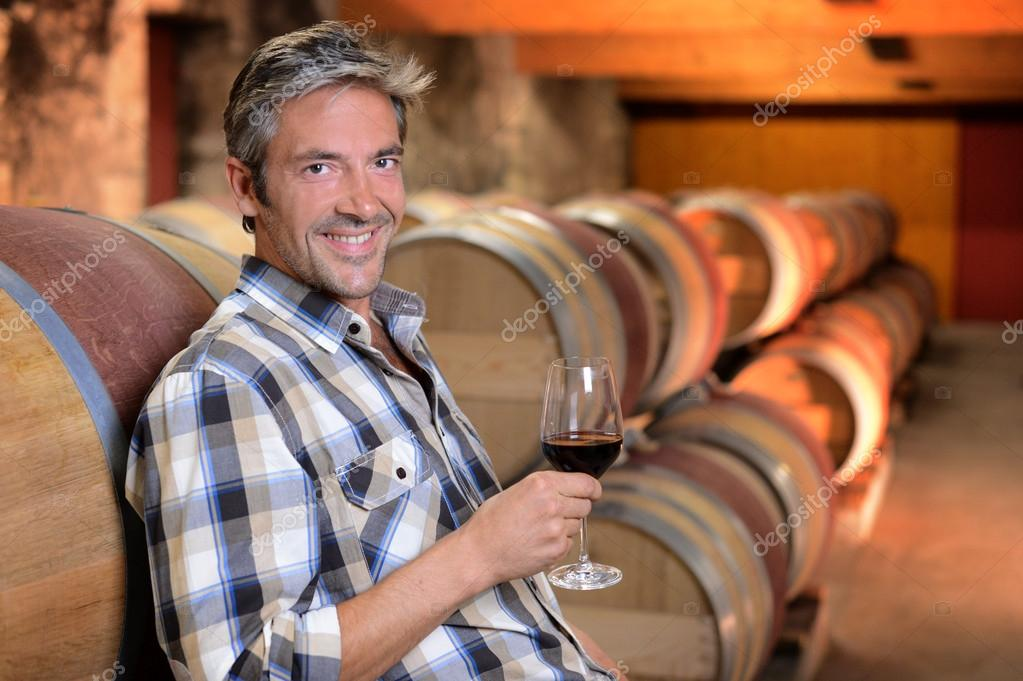 Smiling winemaker standing in wine cellar with glass — Stock Photo #13930463
