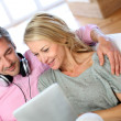 Couple listening to music at home with tablet — Stock Photo #13943069