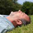 Closeup of senior man sleeping in grass - Photo