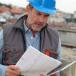 Construction manager controlling building site with plan — Stock Photo #13940135