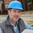 Construction manager controlling building site with plan — Stock Photo