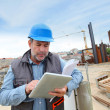 Construction manager controlling building site with plan — Stock Photo #13940150