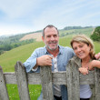 Senior couple leaning on fence in countryside — Stock Photo #13940171