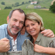 Senior couple leaning on fence in countryside — Stock Photo #13940200