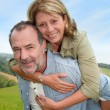 Senior man giving piggyback ride to wife — Stock Photo