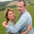Portrait of happy senior couple in countryside — Stock Photo