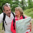 Senior couple rambling in forest with map — Stock Photo #13940432
