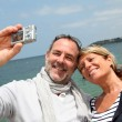 Stock Photo: Retired couple taking picture of themselves by the sea