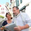 Mature couple in seaside resort looking at map — Stock Photo #13940544