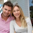 Portrait of smiling couple standing in front of house — Stock Photo #13940747