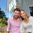 Portrait of smiling couple standing in front of house - Stock Photo