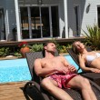 Couple suntanning in long chairs - Photo