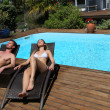 Couple in long chairs by swimming pool - Lizenzfreies Foto
