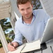 Portrait of smiling man working at home on tablet — Stock Photo