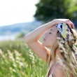 Beautiful blond woman in meadow with modern look - Stock Photo