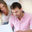 Couple at home using laptop computer — Stock Photo #13941466