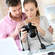 Couple at home looking at pictures on camera and laptop — Stock Photo