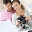 Couple at home looking at pictures on camera and laptop — Stock Photo #13941492