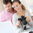 Couple at home looking at pictures on camera and laptop - Stock Photo