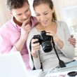 Couple at home looking at pictures on camera and laptop — Stock Photo #13941493