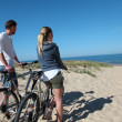 Couple with bicycles looking at the ocean - Stock Photo