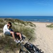 Couple sitting by bicycles on a sand dune — Stock Photo