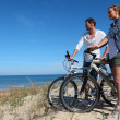 Couple with bicycles looking at the ocean — Стоковая фотография