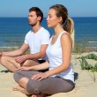 Couple doing yoga exercices on a sandy beach — Stock Photo