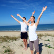 Stock Photo: Couple meditating at the beach with arms up
