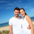 Smiling couple in fitness outfit standing on the beach — Stock Photo