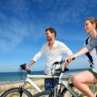 Couple standing on a sand dune with bicycles — Stock fotografie