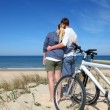 Couple standing by the ocean with bicycles — Stock Photo