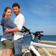 Couple standing by the ocean with bicycles - Stock Photo