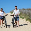 Couple walking on a sandy path with bicycles — Stock Photo