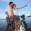 Couple standing on a bridge with bicycles — Stock Photo #13941748