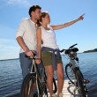Stock Photo: Couple standing on bridge with bicycles