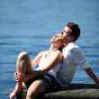 Couple relaxing on a lake bridge in summertime — Stock Photo