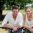 Portrait of cheerful couple riding bicycle in countryside — Stock Photo #13941765