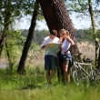 Couple on a bike ride making a stop to look at map — Stock Photo