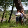 Couple on a bike ride making a stop to look at map — Stock Photo #13941779