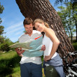 Couple on a bike ride making a stop to look at map — Stock Photo #13941787